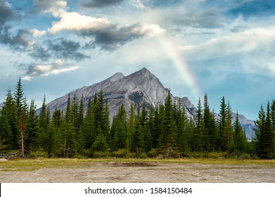 Mount Rundle with pine trees and rainbow in the blue sky at campground in provincial park