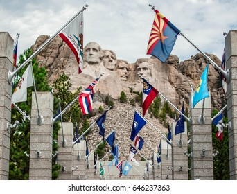 Mount Rushmore with country flags from around the world centered framed shot on a cloudy day.