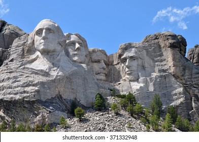 The Mount Rushmore National Monument in the Black Hills of South Dakota. Blue sky with the afternoon sun casting shadows across the famous faces of Lincoln, Roosevelt, Jefferson, and Washington.
