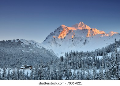 Mount Shuksan winter sunset with ski lodge at the foot of the mountain