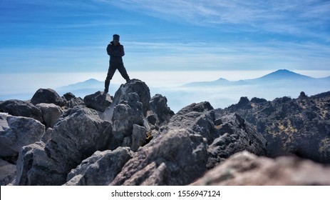 Mount Sumbing, Wonosobo regency, Central Java Indonesia. Sept - 11, 2019. man silhoutte at Mount Sumbing summit, with blue mountain at the background