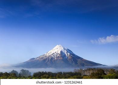 Mount Taranaki with snow capped under the blue sky in Egmont National Park, Taranaki, New Zealand. Stratovolcano cone in New Zealand