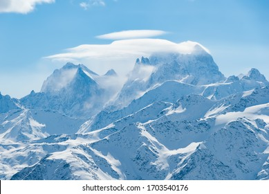Mount Ushba in Caucasus mountains with snowstorm clouds on the ridge. Alpine winter view