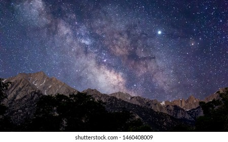 Mount Whitney and it's spires are seen before dawn being lit by sunlight as the Milky Way galaxy illuminates the night sky above the snowy mountains a bright Jupiter is to the right.
