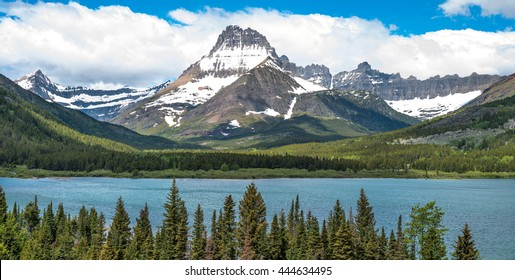 Mount Wilbur - A panoramic spring view of Mount Wilbur rising high at side of Swiftcurrent Lake  in Many Glacier region of Glacier National Park, Montana, USA.