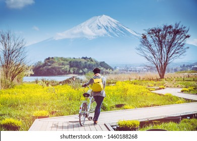 Mountai fuji with snow and flower garden along the wooden bridge at Kawaguchiko lake in japan, Mt Fuji is one of famous place in Japan. A women take a bicycle on wooden bridge.