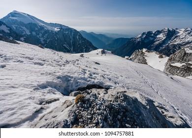 A mountain alpine landscape of Kamnik Savinja alps around Skuta mountain shelter. Snow covered alpine peaks and free public mountain shelter Bivak pod Skuto.