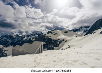 A mountain alpine landscape of Kamnik-Savinja Alps, Slovenia. Peaks around mount Skuta with public shelter bivak pod skuto. Snow covered mountains, blue sky with clouds.