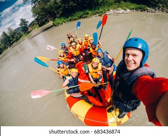 mountain Altai, RUSSIA - July 16, 2017: man in a helmet holds an action camera and makes selfie on the background of friends with oars, rafting