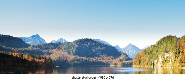 Mountain autumn landscape with colorful forest. Blue sky.