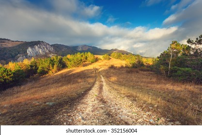 Mountain autumn landscape with road at sunset. Low clouds. Nature background