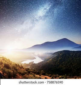 Mountain beautiful landscape with river views, vibrant night sky with stars and nebula and galaxy. Deep sky astrophoto.
