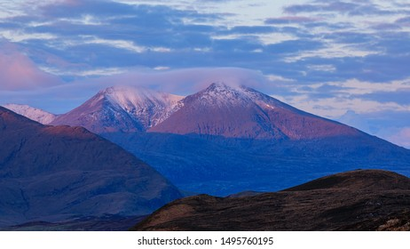 The Mountain Beinn Spionnaidh near Durness at Sunrise. Snow-capped and lit by the rising sun with pink light falling on it and blue skies behind.