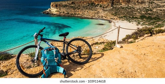 Mountain bicycle and blue backpack, by the sea. Rabbit beach, Lampedusa, Sicily