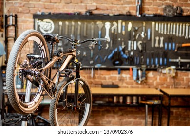 Mountain bicycle during the repairing process hanging on the stand at the workshop