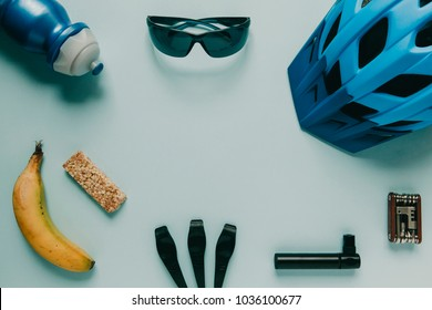 Mountain bike accessories and tools with copy space in the middle, on blue background.