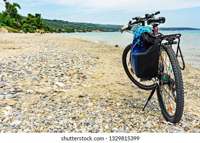 Mountain bike with bag by the sea parked on the beach.