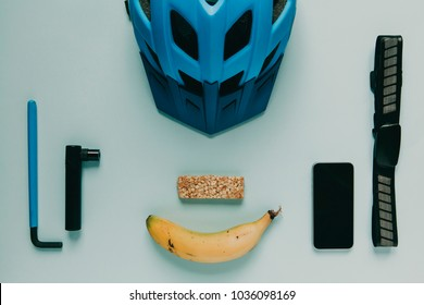 Mountain bike cycling accessories and food prepared for a bike ride, on blue table. - Shutterstock ID 1036098169