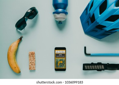 Mountain bike cyclist accessories on white background, and gps route on mobile phone screen. - Shutterstock ID 1036099183