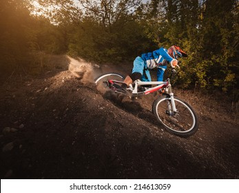 Mountain Bike cyclist riding forest track at sunrise healthy lifestyle active athlete. Downhill biking.