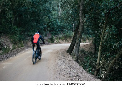 Mountain Bike cyclist riding single track with red jacket