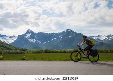 Mountain bike cyclist at sphalt road, Lofoten, Norway
