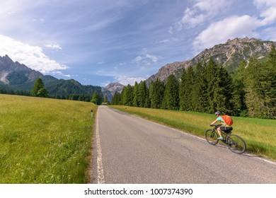 Mountain bike girl on alpine road.