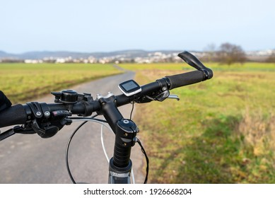 Mountain bike handlebar seen from the first person perspective. Visible bicycle frame and bicycle accessories on the handlebar, and the road in the background.