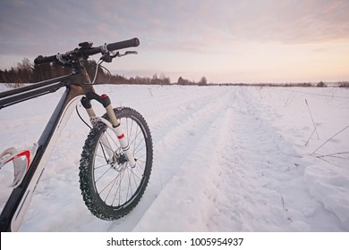 A mountain bike on a snowy road, against a background of sunset. Winter extreme adventures and travel.