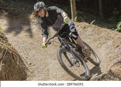 Mountain bike rider rides through a gravity slope of an artificial dirt track. The scene is held in earthy colors.