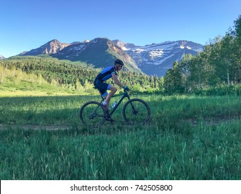 a mountain bike rides in front of an epic mountain vista