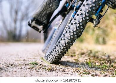 Tiefwinkel des Mountainbike-Reifens, Nahaufnahme auf der Strecke - Fahrradfahrer mtb Außenansicht des Rads auf Kies - Konzept der sportlichen Fahrradaktivität und Reifenleistung - Bild