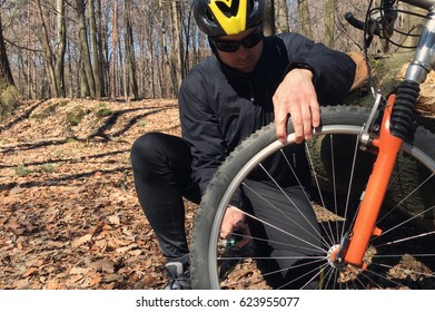 Mountain biker  checking his bicycle tires in a sunny day outdoors.Young man fixing bicycle tire outside.