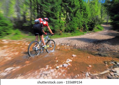 Mountain biker crosses a water stream on the mountain