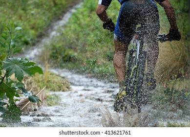 Mountain biker driving in rain upstream creek