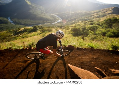 Mountain biker going downhill with a beautiful green valley with a river running through it.
