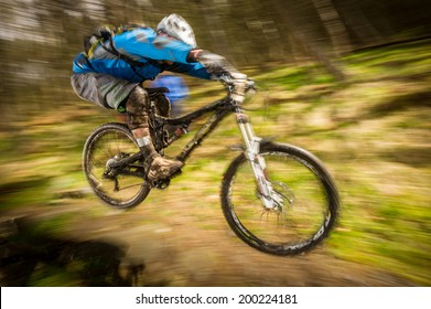 Mountain biker going over a jump in the forest with speed