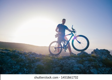 Mountain biker holding his bike on a rough cliff terrain on a sunset.
