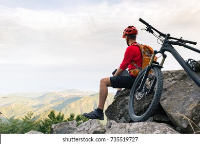 Mountain biker looking at inspiring landscape on bike rocky trail in autumn mountains. Riding on full suspension bike. Sport fitness, motivation and inspiration in beautiful inspirational landscape.