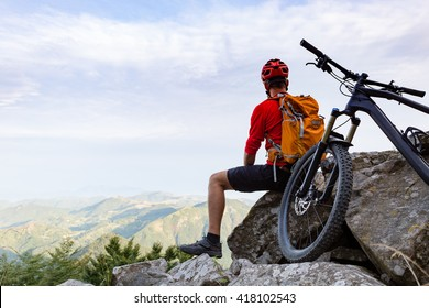 Mountain biker looking at view on bike trail in autumn mountains. Male rider resting on cycling trip in nature. Sport fitness, motivation and inspiration in beautiful inspirational landscape.