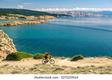 Mountain biker looking at view and traveling on bike in summer sea landscape. Man rider cycling MTB on rocky yellow trail. Fitness motivation, inspiration in beautiful inspirational view.