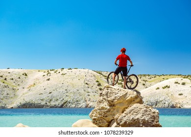 Mountain biker looking at view and traveling on bike in summer sea landscape. Man riding a bicycle in mountains and beach. Fitness motivation, inspiration in beautiful inspirational view.