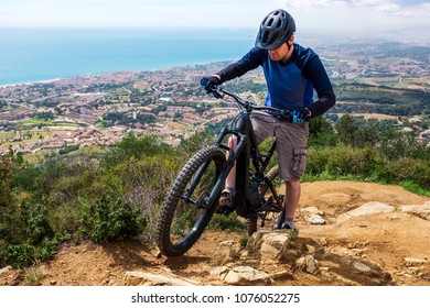 Mountain biker on ebike going uphill on single track with the ocean in the background