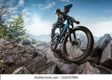 Mountain biker on stone forest trail. Male cyclist rides the rock