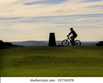a mountain biker on the summit of a hill with sunset clouds behind