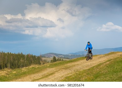 mountain biker on sunny day riding on a winding dirt road in a rural hilly area of green forest against the blue sky with beautiful clouds