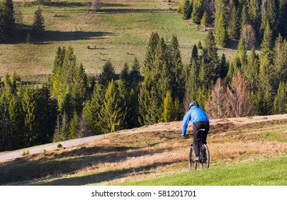 mountain biker on sunny give rides on the rolling hills of green forest