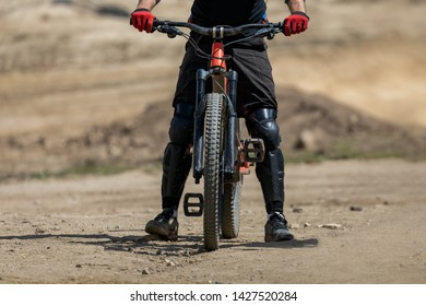 Mountain Biker ready for a run on the track. Close up of front tire and gear.