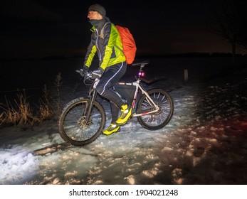 Mountainbiker fahren alleine in schneebedeckter Winternacht. Sportler, die gut für Winterradfahren ausgerüstet sind, radeln im Gelände.  kaltes Winterwetter und Schnee.