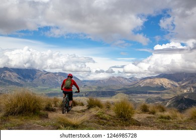 A mountain biker rides along the ridge and descends the mountain with beautiful scenery way down below